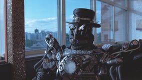 Metaal androïde zitting bij lijst in restaurant met glas wijn op achtergrond van mening van high-rise gebouwen van stad stock footage