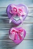 Metaal hart-vormige kleine giftdozen met roze linten op houten Stock Foto