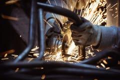 Metaal het malen op staalpijp met flits van vonken en de lijnen van metaal leiden dicht omhoog door buizen Royalty-vrije Stock Foto