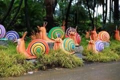 Metaal kleurrijk slakstandbeeld in tuin stock foto