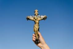Metaal kruis gekruisigde Christus ter beschikking op blauwe hemel Stock Afbeelding