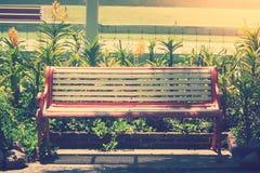 Metaal lange stoel die op concrete vloer naast beautifuktuin bij openbaar park bij platteland plaatsen Royalty-vrije Stock Afbeeldingen