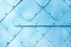 Metaal lichtblauwe oppervlakte van oude gehamerde metaalplaten met klinknagels en architecturale details op hen Stock Afbeelding