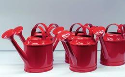 Metaal rode gieters voor het water geven van bloemen en installaties stock foto