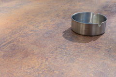 Metaalaluminium Ash Tray op de Achtergrond van de de Bovenkanttextuur van de Koperlijst Royalty-vrije Stock Fotografie