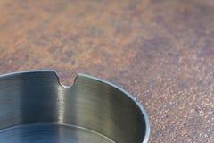 Metaalaluminium Ash Tray op de Achtergrond van de de Bovenkanttextuur van de Koperlijst Royalty-vrije Stock Afbeelding