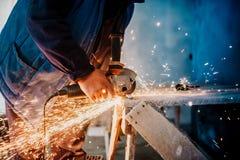 Metaalarbeider scherp ijzer en metaal met een het roterende hoekmolen en werken, die metaalvonken produceren stock foto's
