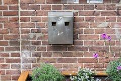 Metaalasbakje op een muur van de baksteensteen met sommige installaties en bloemen stock foto