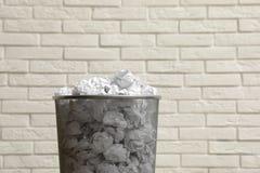 Metaalbak met verfrommeld document tegen bakstenen muur stock afbeelding