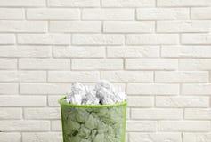 Metaalbak met verfrommeld document tegen bakstenen muur stock foto's