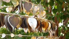 Metaalbladeren met wensen dichtbij tempel Rek met traditionele die metaalbladeren met wensen dichtbij boom in yard van tempel wor stock footage