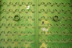 Metaaldeur met een gesmeed patroon en groene verf met ringen voor het kloppen stock foto