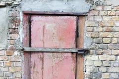 Metaaldeur op de achtergrond van de garagebakstenen muur stock foto's