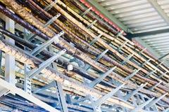 Metaaldraden in een bos Technologische buizen op metaaltribunes met tinetiketten Op de chemische productie van ongebruikelijke st stock fotografie