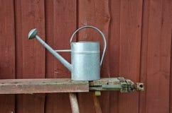 Metaalgieter op bank naast rode houten muur stock foto