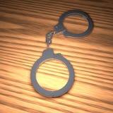Metaalhandcuffs over houten lijst Stock Illustratie