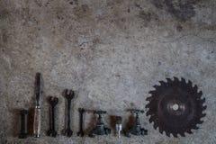 Metaalhulpmiddelen, de kraan van de de beitelmoersleutel van het zaagblad en de gelegde vlakte van boorbeetjes op concre Stock Fotografie