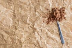 Metaallepel met droog cacaopoeder Op verfrommelde document bruine achtergrond stock afbeeldingen