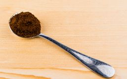 Metaallepel met grondkoffie op lijst Stock Afbeeldingen