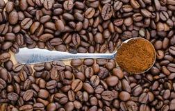 Metaallepel met grondkoffie op lijst met koffiebonen Stock Foto