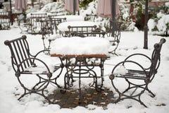 Metaallijst en stoelen met sneeuw wordt behandeld die Royalty-vrije Stock Fotografie