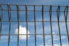 Metaalomheining tegen een blauwe hemel Stock Afbeelding