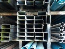 Metaalpijpen en pvc-pijpenstapel op plank Stock Afbeeldingen