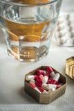 Metaalpillendoosje met witte en rode capsules samen met waterglas royalty-vrije stock afbeelding