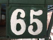 Metaalplaat 65 in wit wordt genummerd dat Stock Afbeelding