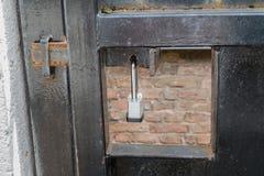 Metaalpoort door hangslot wordt en wordt beveiligd gesloten dat Stock Afbeeldingen