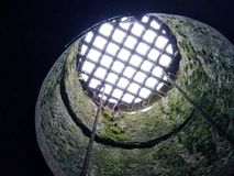 Metaalrooster die een steen behandelen goed met bemoste muren die tot licht en hemel leiden royalty-vrije stock afbeelding