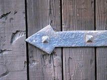 Metaalscharnier met een vorm van een pijl die links over een oude deur richten royalty-vrije stock afbeeldingen