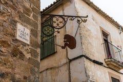 Metaalsilhouet van een gezette aap die van de hoek van Calle del Mono in de Oude Stad van Caceres hangen stock afbeeldingen