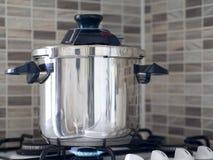 Metaalstaalhogedrukpan die zich op de oven in de keuken en het koken wordt gekookt bevinden royalty-vrije stock fotografie