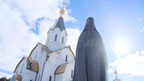 Metaalstandbeeld van priester op achtergrond van kerk Voorraadlengte Mooi standbeeld van heilige minister met duidelijke details stock footage