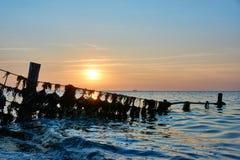 Metaalstructuur met plastic afval in overzees bij zonsondergang royalty-vrije stock foto