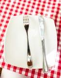 Metaalvork en mes die op witte plaat bij geruite rode doek liggen Stock Foto
