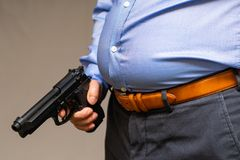 Big fat belly of a Japanese male in a blue shirt, holding a gun. Metabolic Japanese male, close-up of a big fat belly Royalty Free Stock Photo