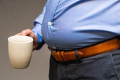 Big fat belly of a Japanese male in a blue shirt, holding a white cup. Metabolic Japanese male, close-up of a big fat belly Stock Images