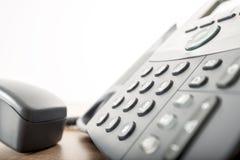 Metad sikt för slut upp av en svart landlinetelefon med ett nummer Arkivfoton