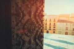 A metade abriu a porta decorativa embutida velha do ferro forjado em Girona Imagens de Stock