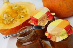 Metade da abóbora cortada e dos três frascos do doce de fruta Imagens de Stock Royalty Free