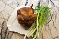 A metade da galinha suculenta grelhada apetitosa com a crosta marrom dourada serviu com fatias e salsa do cal na placa branca, na imagens de stock