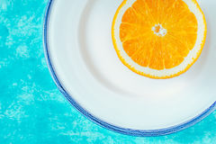 Metade da laranja na placa branca no fundo ciano horizontal fotografia de stock royalty free