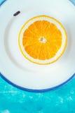 Metade da laranja na placa branca no vertical ciano do fundo foto de stock