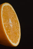 Metade da laranja no fundo escuro Fotografia de Stock Royalty Free