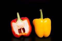 Metade da pimenta no fundo preto puro Pimentas amarelas e vermelhas cortadas ao meio Foto de Stock
