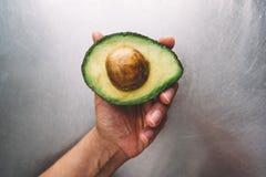 Metade de um abacate em uma mão no fundo de uma opinião de tampo da mesa de aço horizontal, café da manhã saudável fresco do alim fotografia de stock royalty free