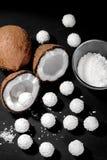Metade de um coco e muitos doces do coco em um fundo preto imagens de stock royalty free