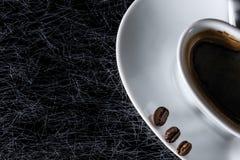 A metade de um coração deu forma ao copo de café com os feijões de café preto em um fundo preto com fresta de esperança foto de stock royalty free